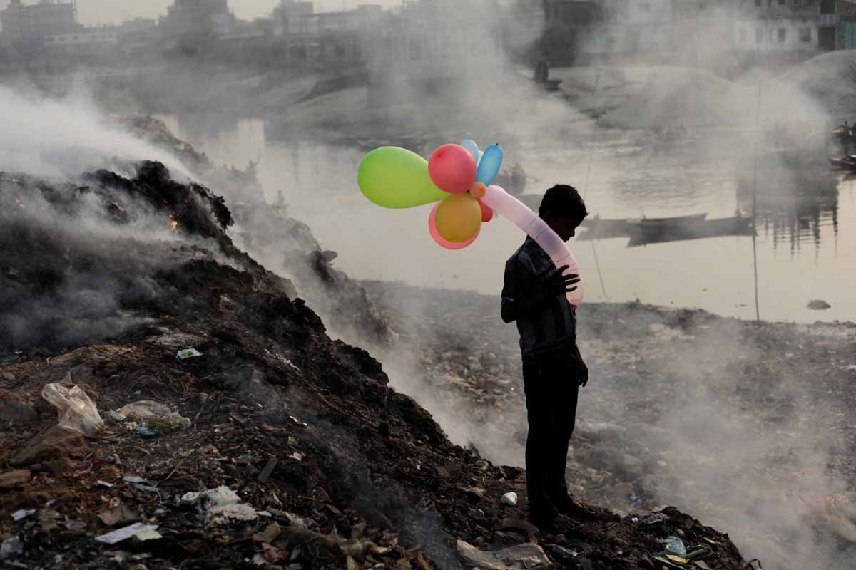 honorable-mention-people-a-boy-plays-with-balloons-by-buriganga-river-as-smoke-emits-from-a-dump-yard-during-sunset-in-dhaka-bangladesh--andrew-biraj-life-along-the-polluted-river.jpg
